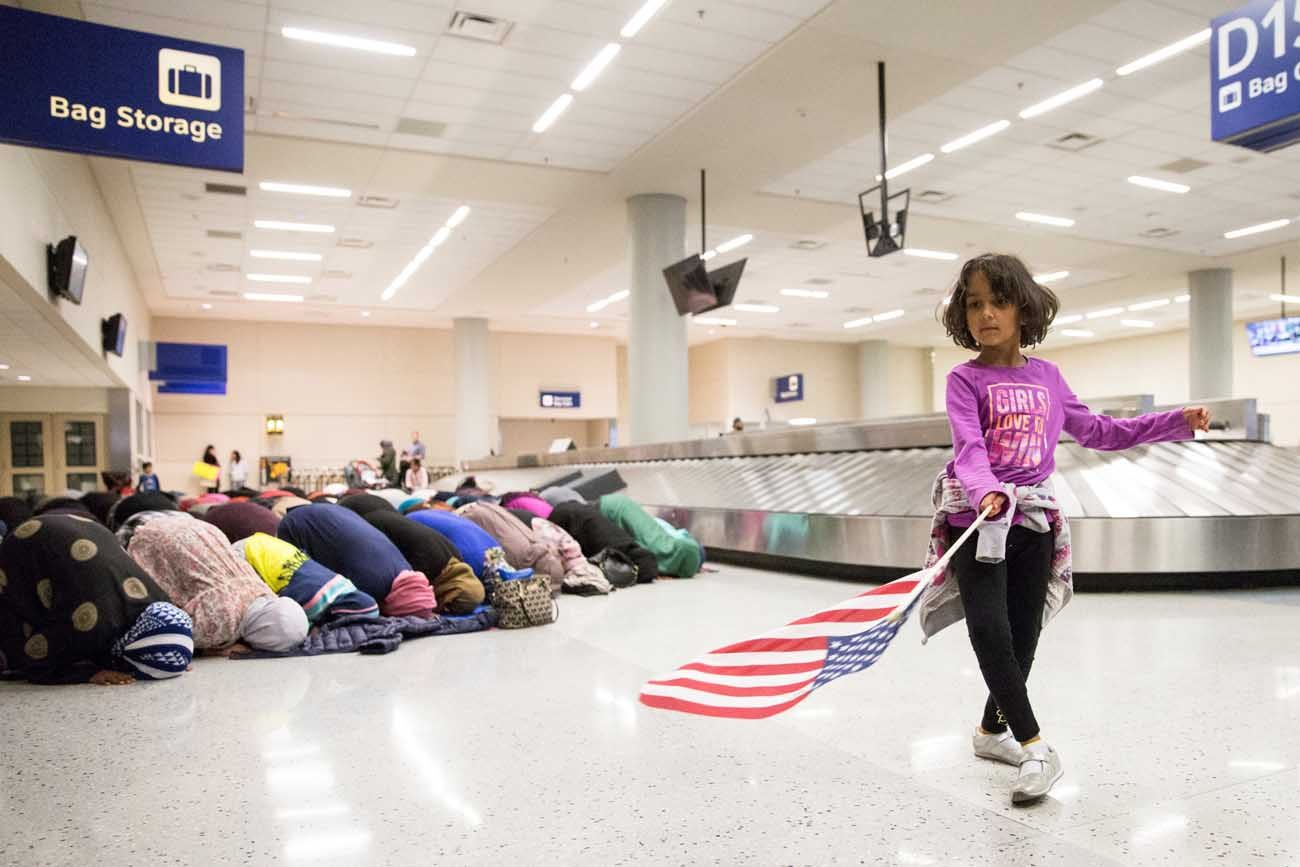 A young girl dances with an American flag at Dallas/Fort Worth International Airport in Dallas Jan. 29 as women pray during a protest against a travel ban imposed by U.S. President Donald Trump's executive action. (CNS photo/Laura Beckman, Reuters)