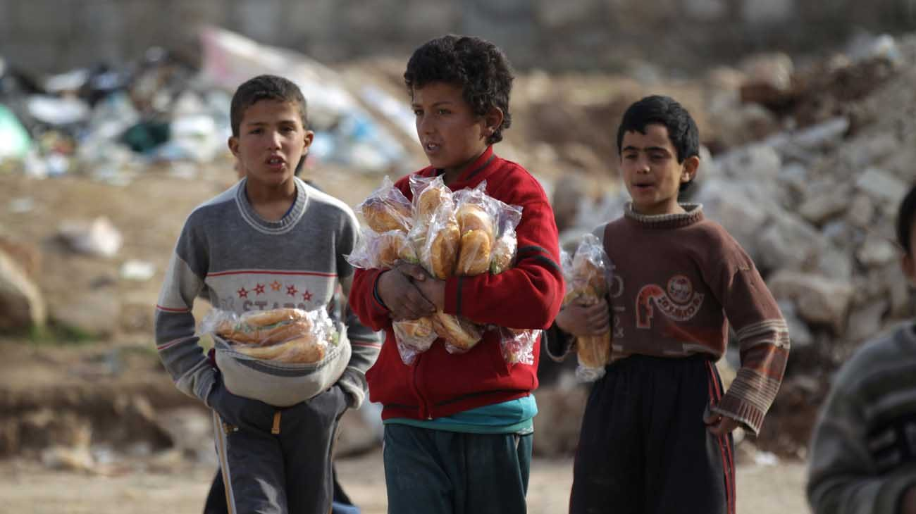 Boys carry sandwiches Jan. 20 in Aleppo, Syria. Conveying Pope Francis' closeness to the Syrian people, a Vatican delegation visited Aleppo Jan. 18-23 following the end of the hostilities that left thousands dead and the city in ruins. (CNS photo/Khalil Ashawi, Reuters)