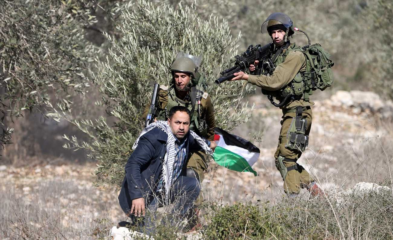 Israeli soldiers detain a Palestinian man during clashes following a protest against the nearby Jewish settlement in the West Bank village of Kafr. The Vatican's hopes for a peace-filled world and its defense of the right to religious freedom have supported its consistent position on the Israeli-Palestinian conflict for 70 years. (CNS photo/Mohamad Torokman, Reuters)