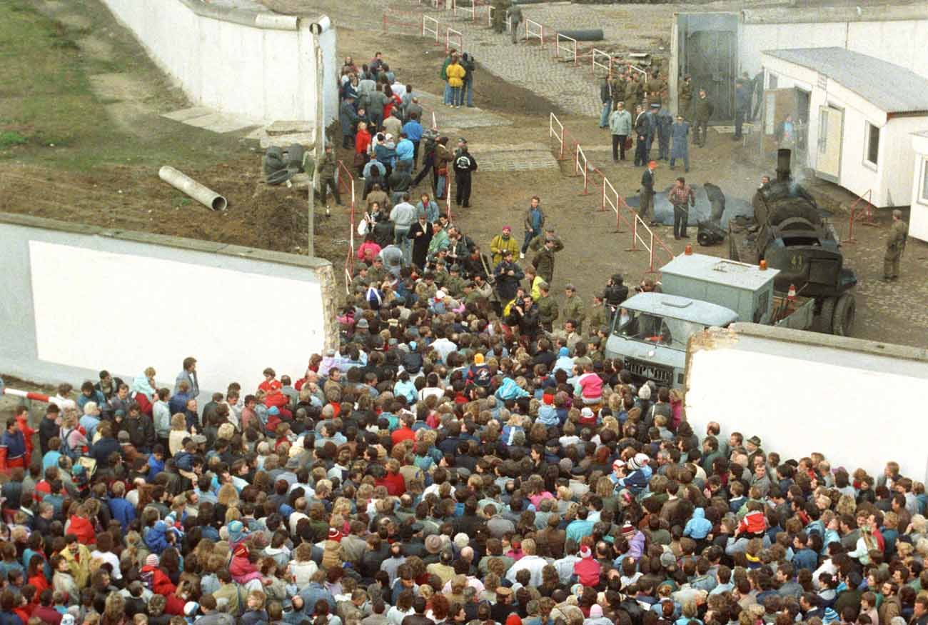 Numerous people walk through a gap in the Berlin Wall at the Bernauer Strasse in Berlin Nov. 10, 1989, after the border was opened. The prayer intentions written by Germans for the 2017 Week of Prayer for Christian Unity call to mind the Berlin Wall. (CNS photo/Wolfgang Kumm, EPA)