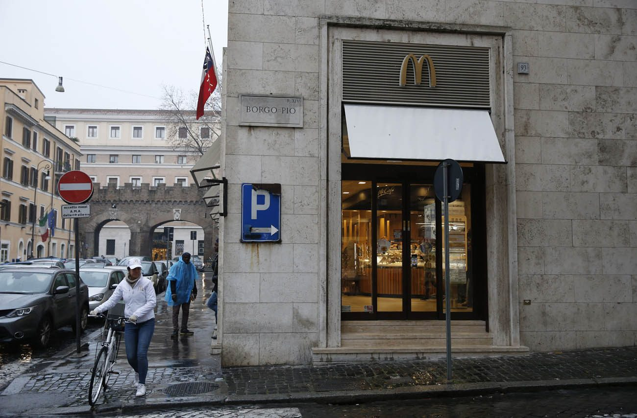 "A worker crosses the street with her bike outside the newly opened McDonald's near the Vatican Jan. 12. The McDonald's will collaborate with Italian aid organization, ""Medicinia Solidale,"" and the papal almoner's office to help feed the poor and homeless around the Vatican. (CNS photo/Paul Haring)"