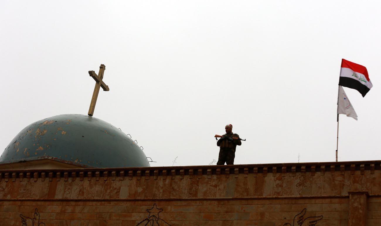 An Iraqi soldier stands guard during Christmas celebrations at the al-Tahira al-Kubra church in al-Hamdaniya, east of Mosul, Dec. 25, 2016. (CNS photo/Ahmed Jalil, EPA)