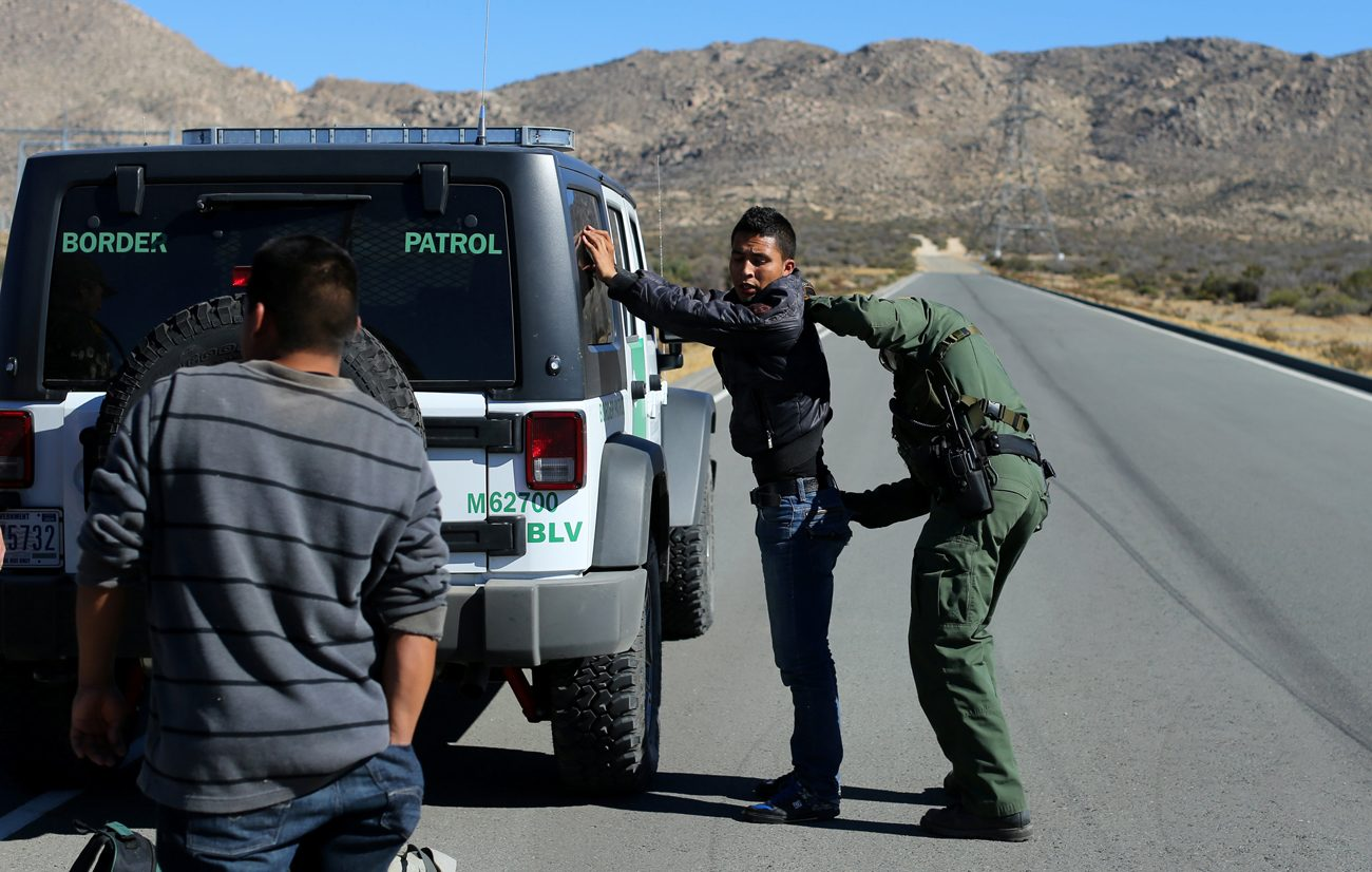 A U.S. Border Patrol agent frisks a man Jan. 11 near the U.S.-Mexico border fence in Jacumba, Calif. The U.S. Catholic bishops remain hopeful that an immigration reform bill will pass. (CNS photo/Mike Blake, Reuters)