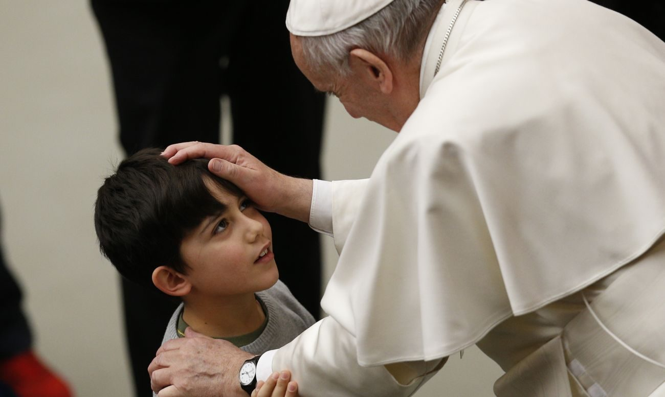 Pope Francis blesses a boy while meeting the disabled during his general audience in Paul VI hall at the Vatican in this Feb. 8, 2017, file photo. Discernment is needed to understand life's ambiguities, not rigid thinking that tends to silence the Holy Spirit, Pope Francis said.(CNS photo/Paul Haring)