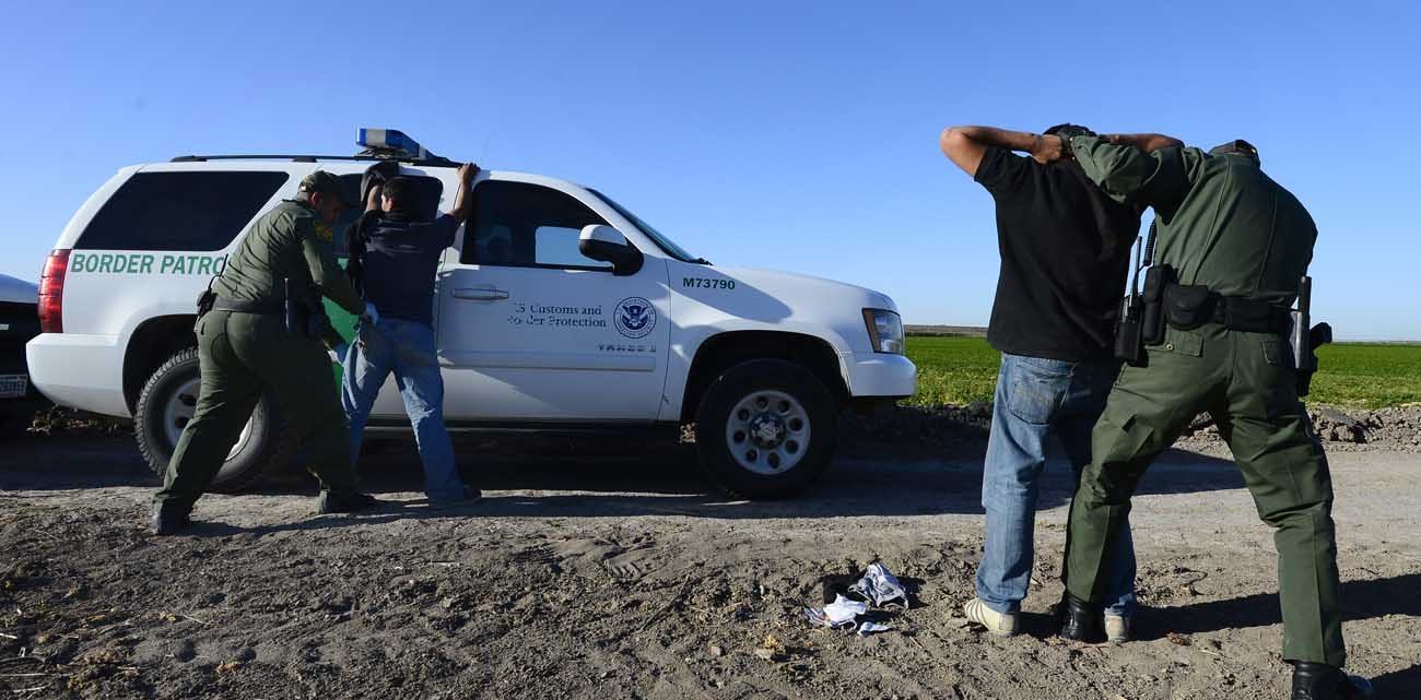 "U.S. Border Patrol agents apprehend and search two people in 2013 who were suspected of entering the U.S. illegally by crossing the Rio Grande River near McAllen, Texas. In a joint statement, Catholic bishops whose dioceses are along the U.S.-Mexico border called for respecting people's dignity regardless of ""migration condition."" (CNS photo/Larry W. Smith, EPA)"