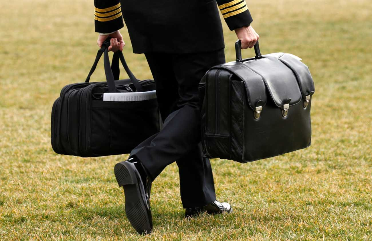 """A military aide, carrying the """"football"""" containing launch codes for nuclear weapons, accompanies U.S. President Donald Trump onto Marine One upon Trump's departure from the White House. The chairman of a U.S. bishops' committee urged Secretary of State Rex Tillerson to pursue additional reductions in the nuclear arsenals of the United States and Russia. (CNS photo/Kevin Lamarque, Reuters)"""