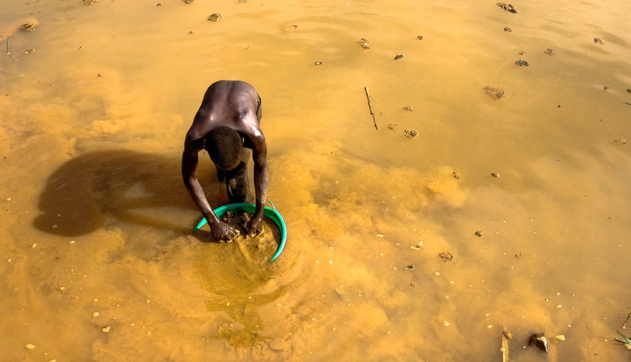 """A Congolese mine worker rinses gold-rich earth out of the pit for water processing in 2009 in Chudja. Church leaders say telling companies they no longer had to disclose whether their firms use """"conflict minerals"""" would be a bad move. (CNS photo/Marc Hofer, EPA)"""