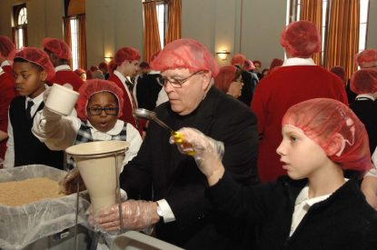 Archbishop Charles Chaput works with students to fill bags of food during the Helping Hands activity Feb. 2 at St. Charles Borromeo Seminary. (D'Mont Reese)