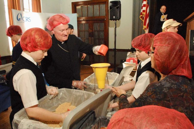 Bishop Michael Fitzgerald helps students package meals for needy people overseas through the schools' partnership with Catholic Relief Services.