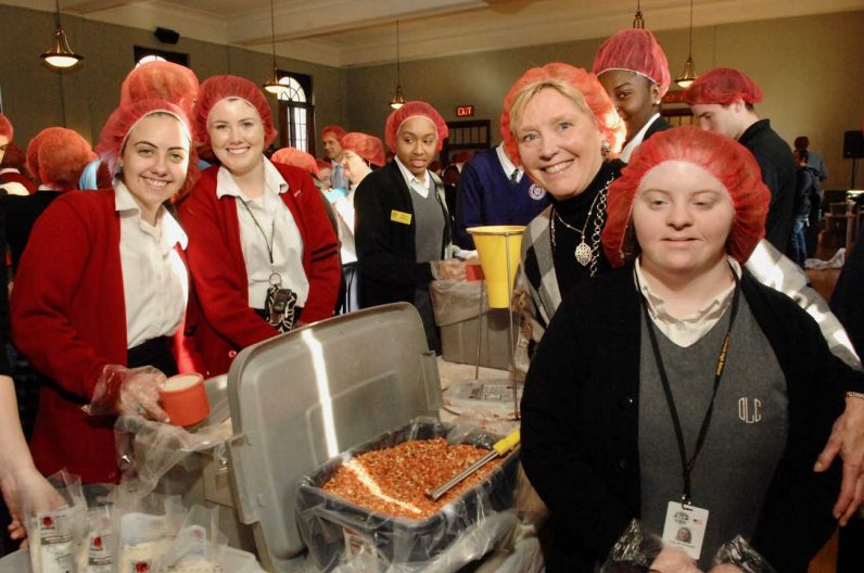 Maureen McCullough helps make meals with Catholic high school and special education students.