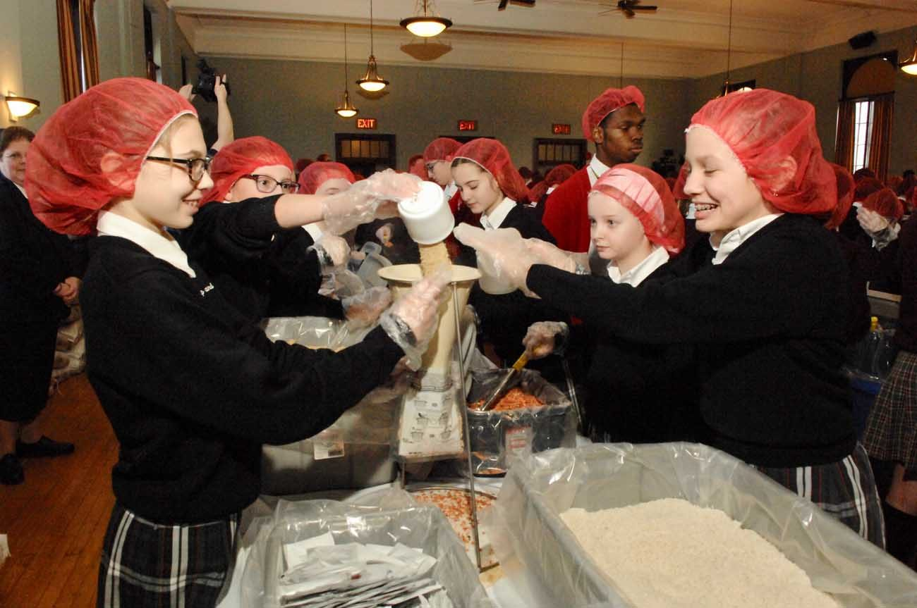 Students fill one of 50,000 meal bags during the Helping Hands activity Feb. 2 at St. Charles Borromeo Seminary. Each bag will feed a family of six, and all will be delivered to Catholic Relief Services clients in Burkina Faso, West Africa. (Photo by D'Mont Reese)