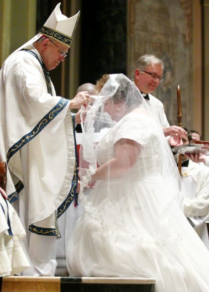Archbishop Charles Chaput places a veil on Jen Settle as she takes her promise to live as a consecrated virgin. (Sarah Webb)