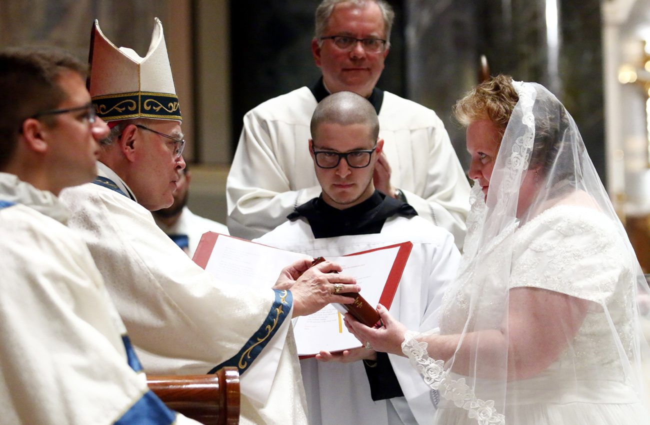 Archbishop Charles Chaput gives the Liturgy of the Hours, the daily prayer of the church, to Jennifer Settle during the liturgy at which she was consecrated to perpetual virginity.