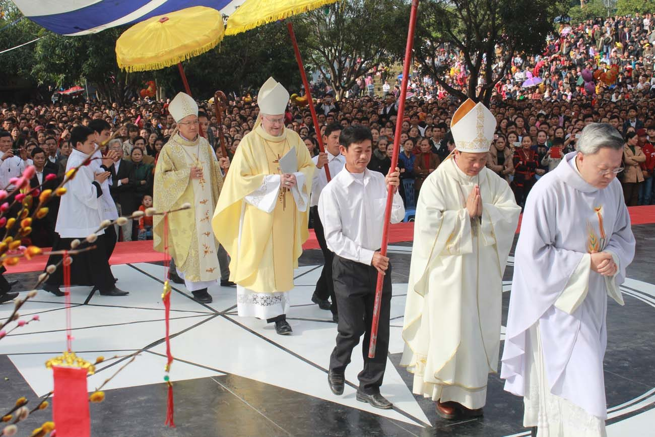 Archbishop Joseph E. Kurtz of Louisville, Ky., left center, arrives to concelebrate Mass Jan. 30 at St. Anthony shrine in Xuan Loc, Vietnam. During his Jan. 24-30 visit, Archbishop Kurtz also met with the Vietnamese bishops' conference president, spoke with the U.S. Embassy deputy chief and spent time with Servants of Jesus sisters and some seminarians. (CNS photo/Archdiocese of Louisville)