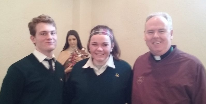 Lansdale Catholic school minister Father John Nordeman and seniors Pat McCabe and Mary Kate Burger pose for a photo int he school chapel, along with a statue of St. Therese.