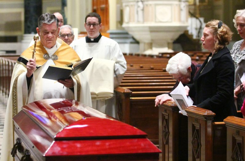 Msgr. Daniel Sullivan, vicar for clergy of the Archdiocese of Philadelphia, blesses the casket of Bishop Martin Lohmuller prior to mid-morning prayer and viewing. (Sarah Webb)