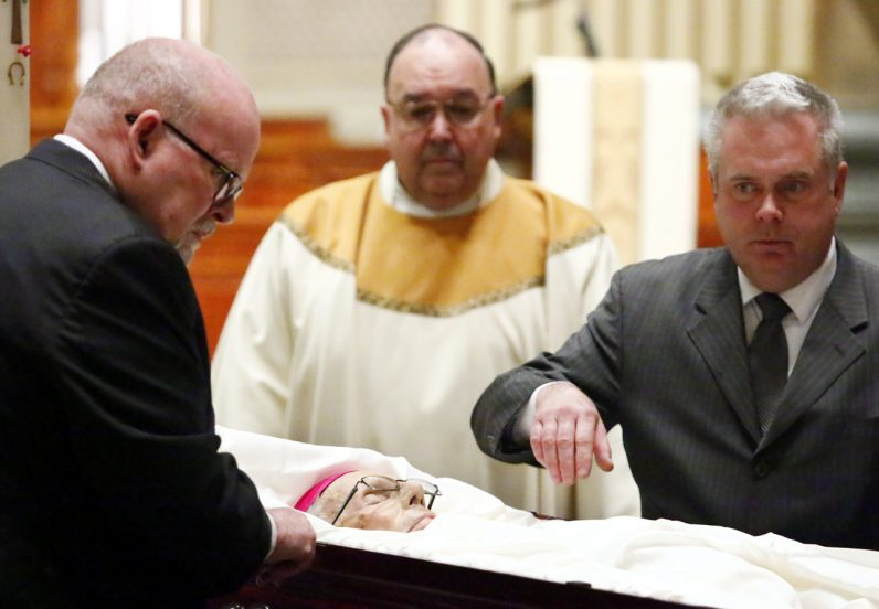 Msgr. Robert Powell looks on as Bishop Lohmuller's casket is prepared for the funeral Mass.
