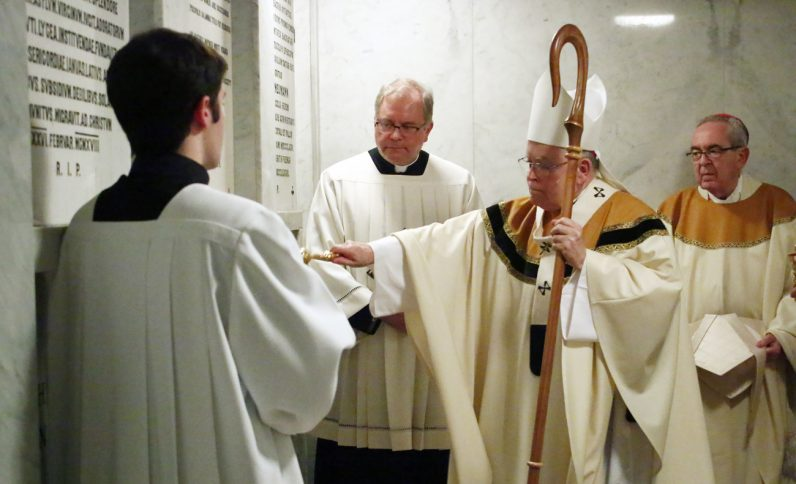 Archbishop Charles Chaput blesses the tomb of Bishop Martin Lohmuller as Cardinal Justin Rigali (right), retired archbishop, looks on.