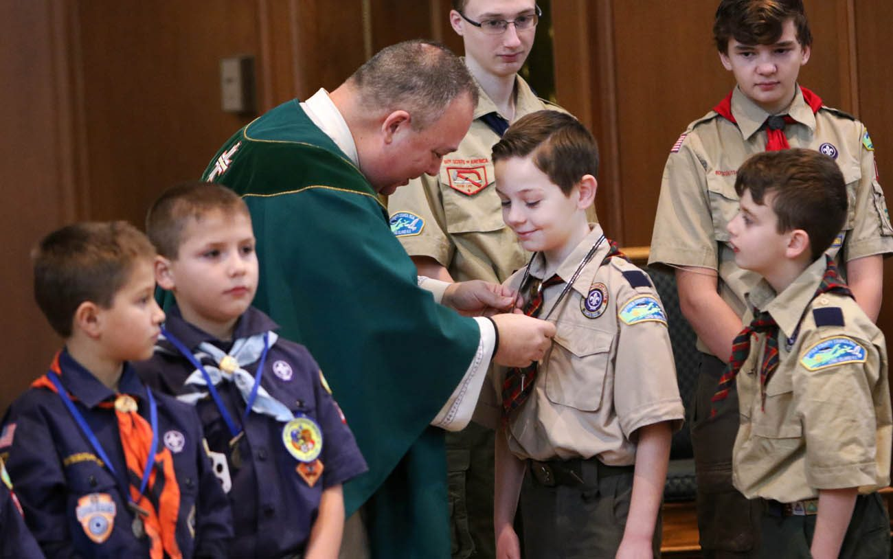 Father Sean Gann presents Children of God and Light of Christ medals to Scout honorees during a Mass marking Scout Sunday at St. Joseph Church in Kings Park, N.Y., Feb. 5. Scout Sunday is celebrated annually by the Boy Scouts of America to recognize the contributions of young people and adults to Scouting. (CNS photo/Gregory A. Shemitz)