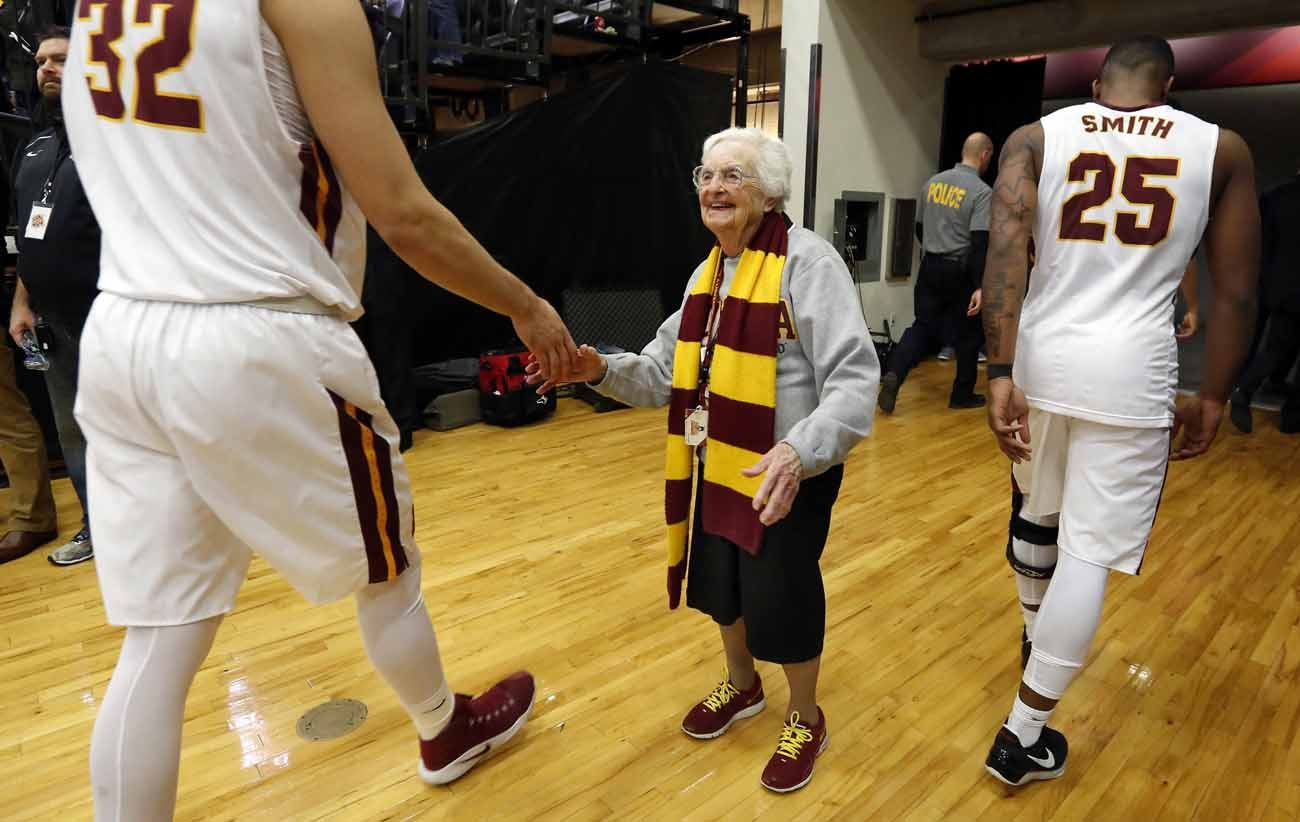 Longtime chaplaain of the Loyola University Chicago men's basketball team and campus icon, Sister Jean Dolores Schmidt, 97, greets players after a game Feb. 12. She is the newest member of the school's sports hall of fame. (CNS photo/Karen Callaway, Chicago Catholic)