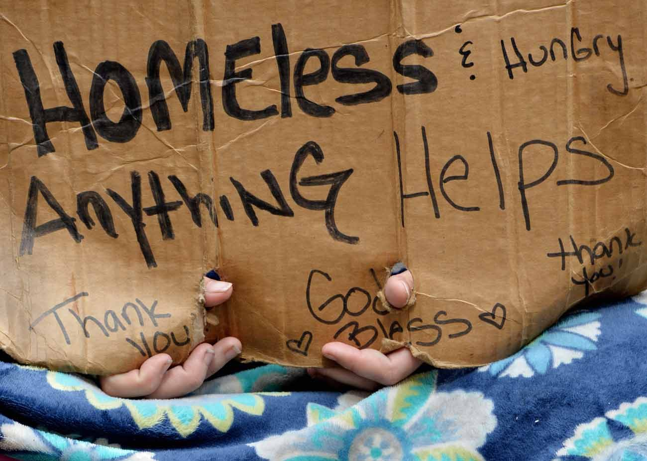A homeless person holds a sign in 2014 while sitting on a sidewalk in New York. As Catholic Charities of the Archdiocese of New York opened its centennial year, the archdiocese launched a campaign to raise $100 million by 2022 for services and opportunities for children and families, especially the poorest and most vulnerable. (CNS photo/Justin Lane, EPA)