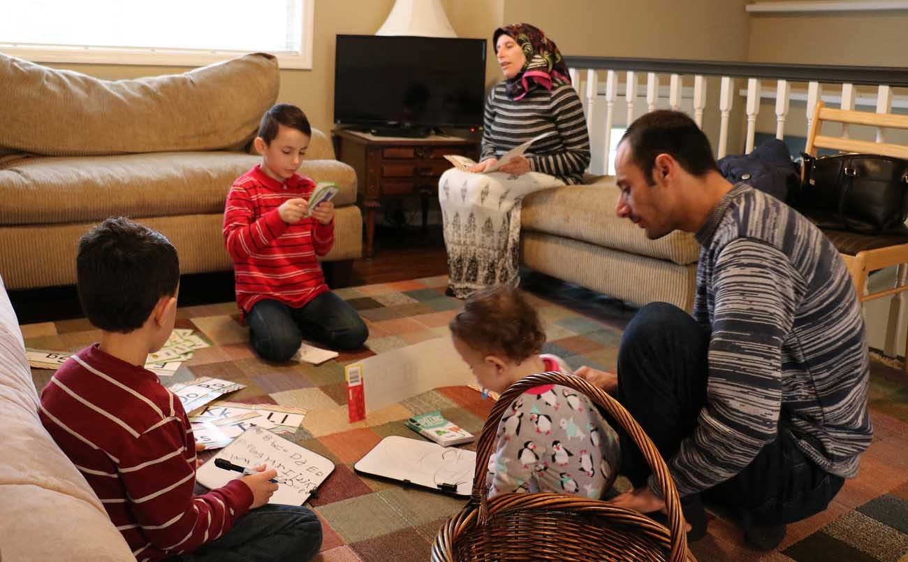 Syrian refugees Ahmed Al Kango and his wife, Sahar, help their children learn English Feb. 7 in their home in Elkhorn, Neb. Pictured from left, the children are Mohamad, Ghaith and Abdulrazzaq. (CNS photo/Joe Ruff, Catholic Voice)