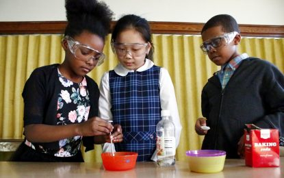 Learning about chemical reactions through the STEM program at St Helena's Out of School Time program are, from left, Faith Theodore (second grade), Sophia Le (third grade) and Christian Robinson (second grade). (Photo by Sarah Webb)