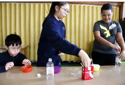 From left, Thomas Nguyen (sixth grade), Tina Nguyen (fifth grade) and Angel Garcia (fifth grade) mix baking soda and vinegar as part of a STEM experiment at St. Helena's OST program. (Sarah Webb)