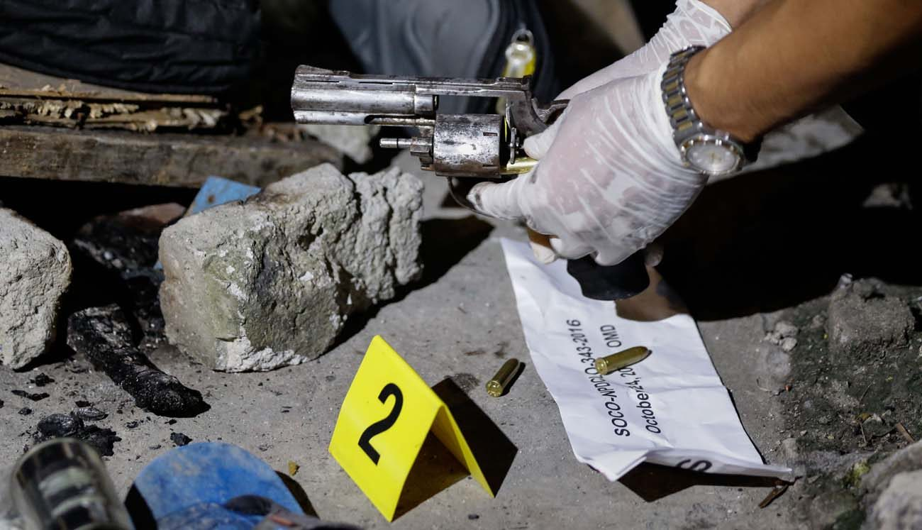A Philippine crime scene investigator inspects a gun used in a 2016 murder in Novaliches. A Philippine cardinal has urged the faithful of his country to tell their lawmakers that the death penalty does not deter violent crime, could potentially legitimize violence and that life is a gift from God. (CNS photo/Mark A. Cristino, EPA)