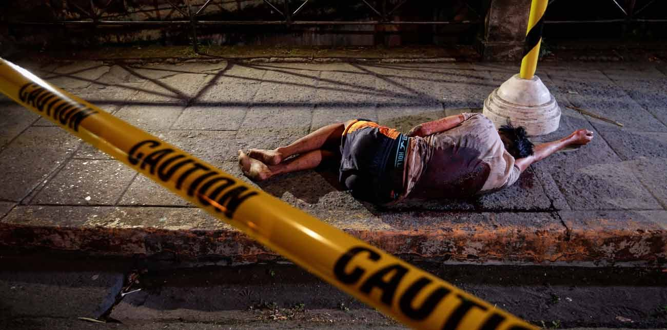 """A man allegedly involved in drug dealing or usage lies lifeless on a street after being shot down by an unidentified gunman in 2016 in Manila, Philippines. Expressing concern about thousands of deaths in the nation's so-called """"war on drugs,"""" the president of the Philippine bishops' conference has sought courage from a deceased cardinal whose influence helped overthrow a dictator in the mid-1980s. (CNS photo/Mark R, Cristino, EPA)"""