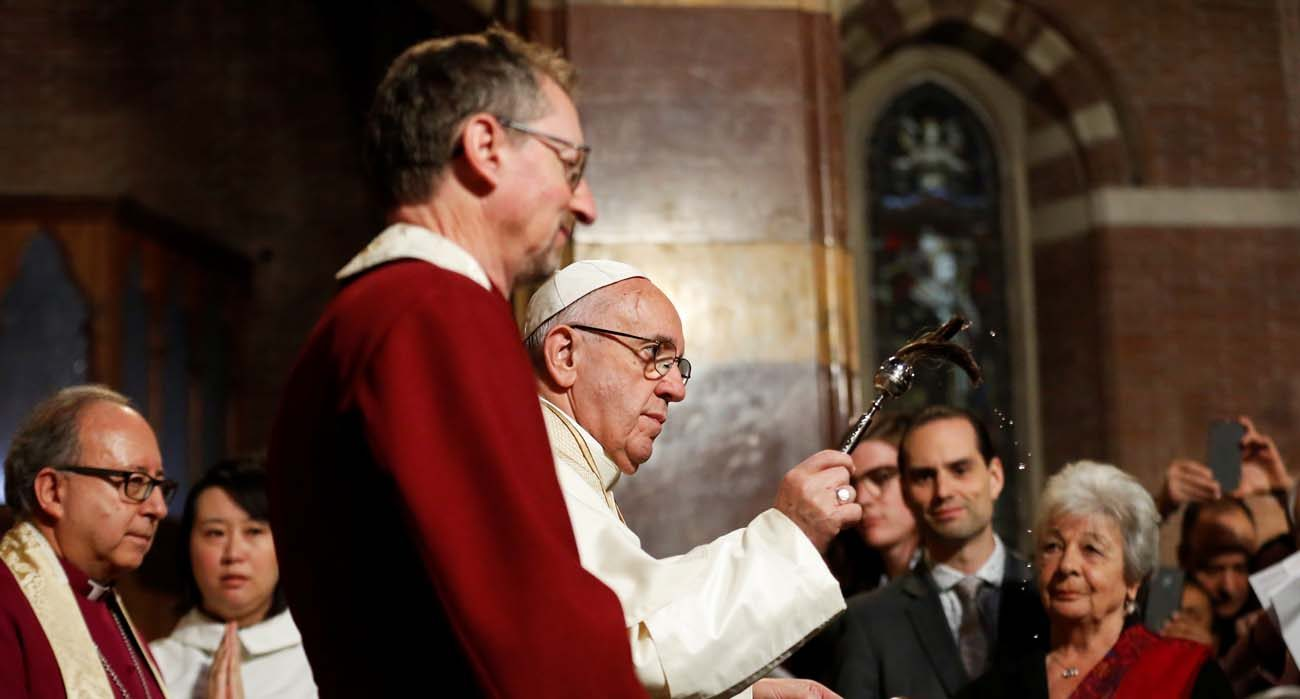 Pope Francis is flanked by Anglican Bishop Robert Innes of the Church of England's Diocese in Europe, as he blesses the congregation with holy water during his visit All Saints' Anglican Church in Rome Feb. 26. It was the first time a pope has visited an Anglican place of worship in Rome. (CNS photo/Alessandro Bianchi, Reuters)
