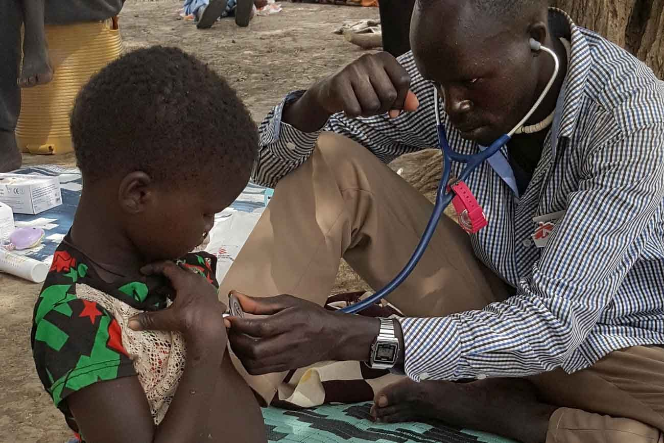 A health worker examines a 4-year-old girl suffering from malnutrition Feb. 13 in Dablual, South Sudan. Pope Francis appealed for humanitarian assistance to South Sudan, where famine threatens the lives of millions of people already suffering due to a three-year civil war. (CNS photo/Nicolas Peissel, handout via EPA)