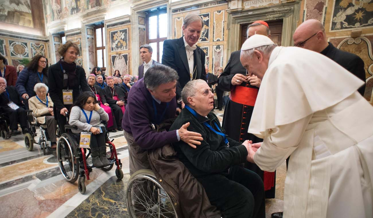 Pope Francis greets a person in a wheelchair Feb. 10 during a Vatican audience with people attending a meeting on health care ministry. The pope said a nation's health care system cannot be run simply as a business because human lives are at stake. (CNS photo/L'Osservatore Romano)