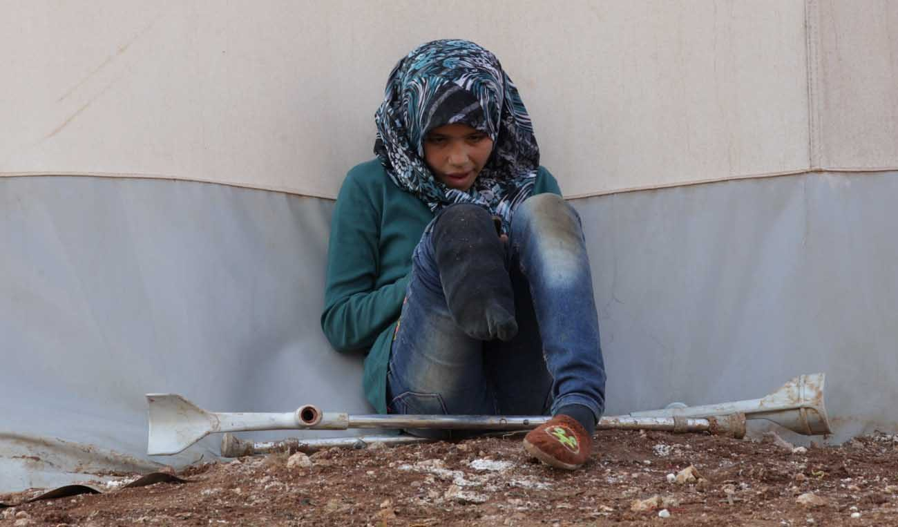 """A Syrian girl with an amputated leg sits outside a tent Jan. 19 at Syria's Bab Al-Salam camp for displaced in Azaz, near the Turkish border. When it comes to helping the poor, the marginalized and refugees, Pope Francis urged Catholics not to mimic the """"Mannequin Challenge"""" by just looking on, frozen and immobile. (CNS photo/Khalil Ashawi, Reuters)"""