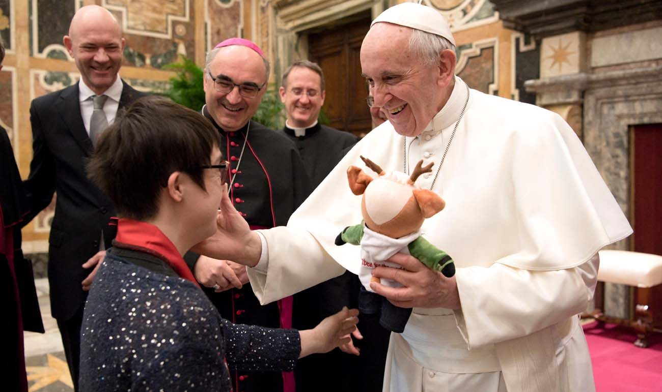 Pope receives a stuffed animal from a participant in the Special Olympics during a meeting Feb. 16 at the Vatican. The athletes and organizers were at the Vatican to promote the Special Olympics World Winter Games, which will be held in Austria March 14-25. (CNS photo/L'Osservatore Romano, handout)