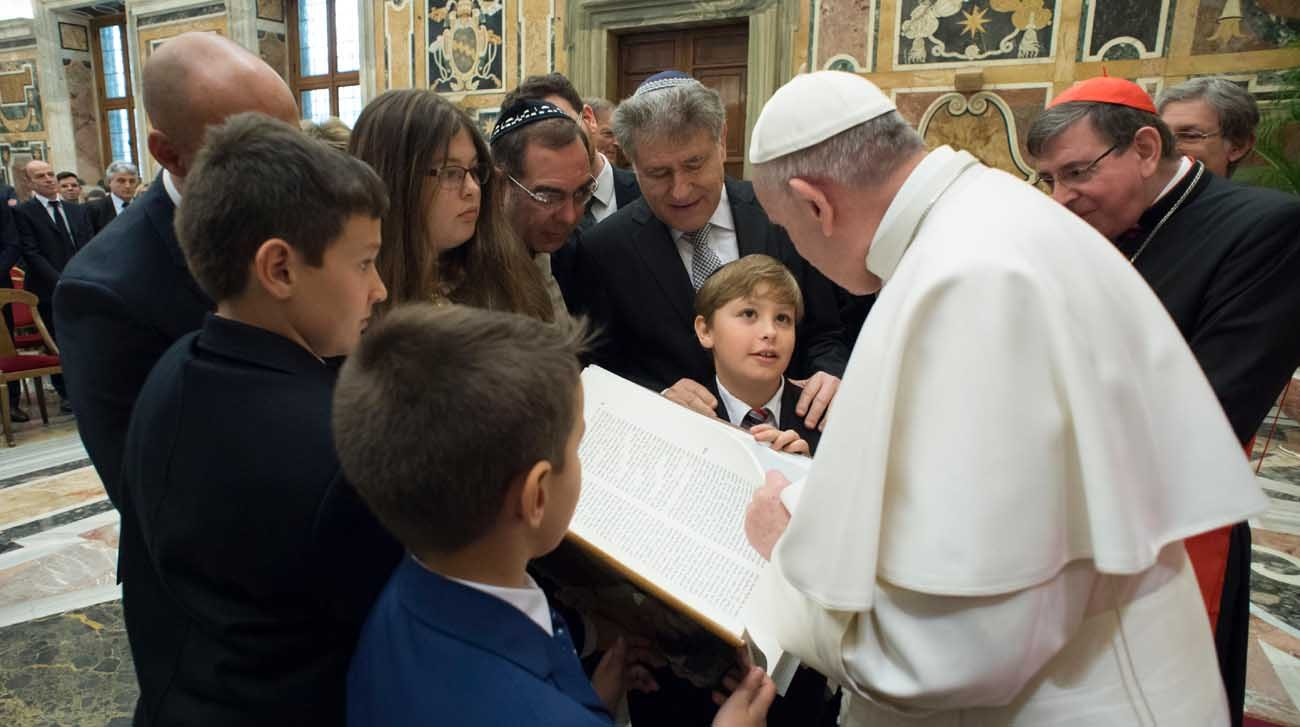 Pope Francis accepts an illustrated copy of the Torah during a meeting with Rabbi Abraham Skorka, center, and an interreligious group of scholars at the Vatican Feb. 23. Rabbi Skorka, rector of the Latin American Rabbinical Seminary and a longtime friend of the pope, led the group in presenting the Torah to the pope. (CNS photo/L'Osservatore Romano)