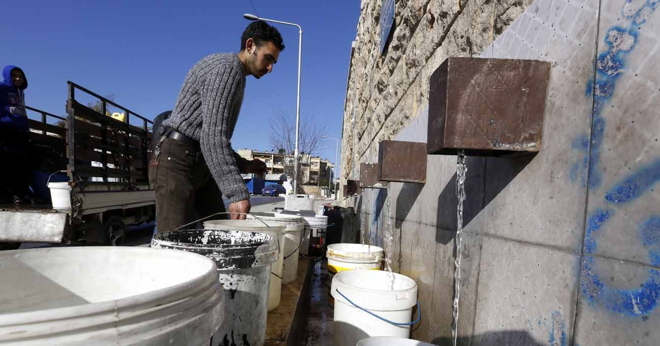 "A man fills buckets with drinking water a a public filling area Feb. 3 in Aleppo, Syria. Access to clean drinking water is a basic human right and a key component in protecting human life, Pope Francis said Feb. 24 during a meeting with 90 international experts participating in a ""Dialogue on Water"" at the Pontifical Academy of Sciences. (CNS photo/Youssef Badawi, EPA)"