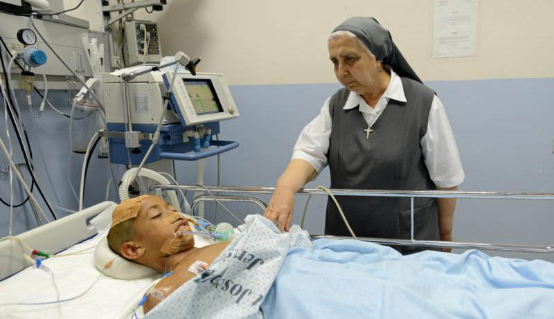Sister Gilbert Saliba, a member of the Sisters of St. Joseph of the Apparition, visits Nidal Alawi, 11, of Gaza, in the intensive care unit of St. Joseph Hospital in Jerusalem July 30, 2014. The effect of prayer can enable the patient to accept a diagnosis, reduce stress and focus energy toward healing -- all important in coping with a health crisis. (CNS photo/Debbie Hill)