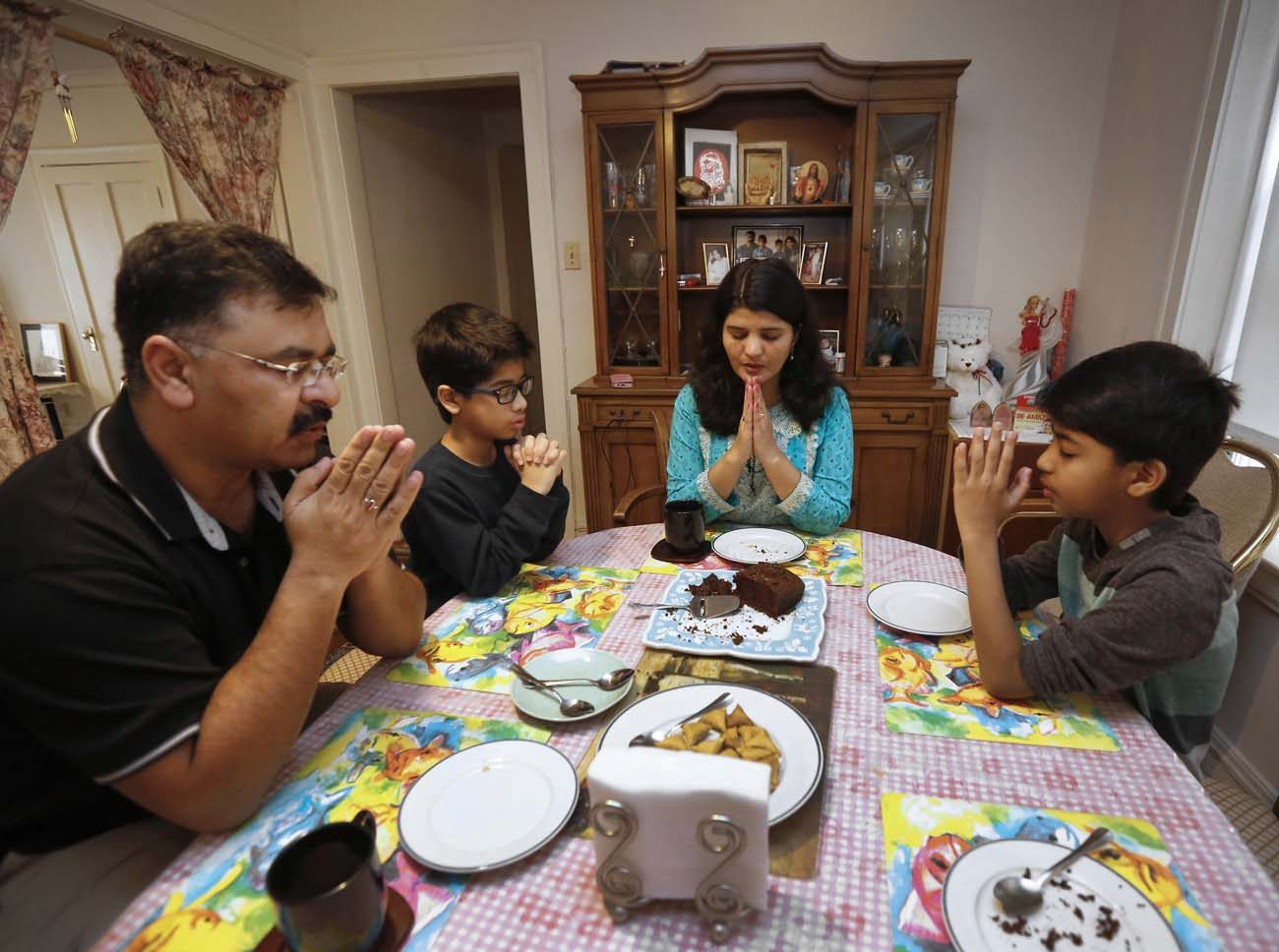Members of the Sharif family share tea at their home in Chicago Feb. 4. They made their way to the United States from Pakistan 20 months ago after being targeted and threatened by a Muslim extremist group. (CNS photo/Karen Callaway, Chicago Catholic)