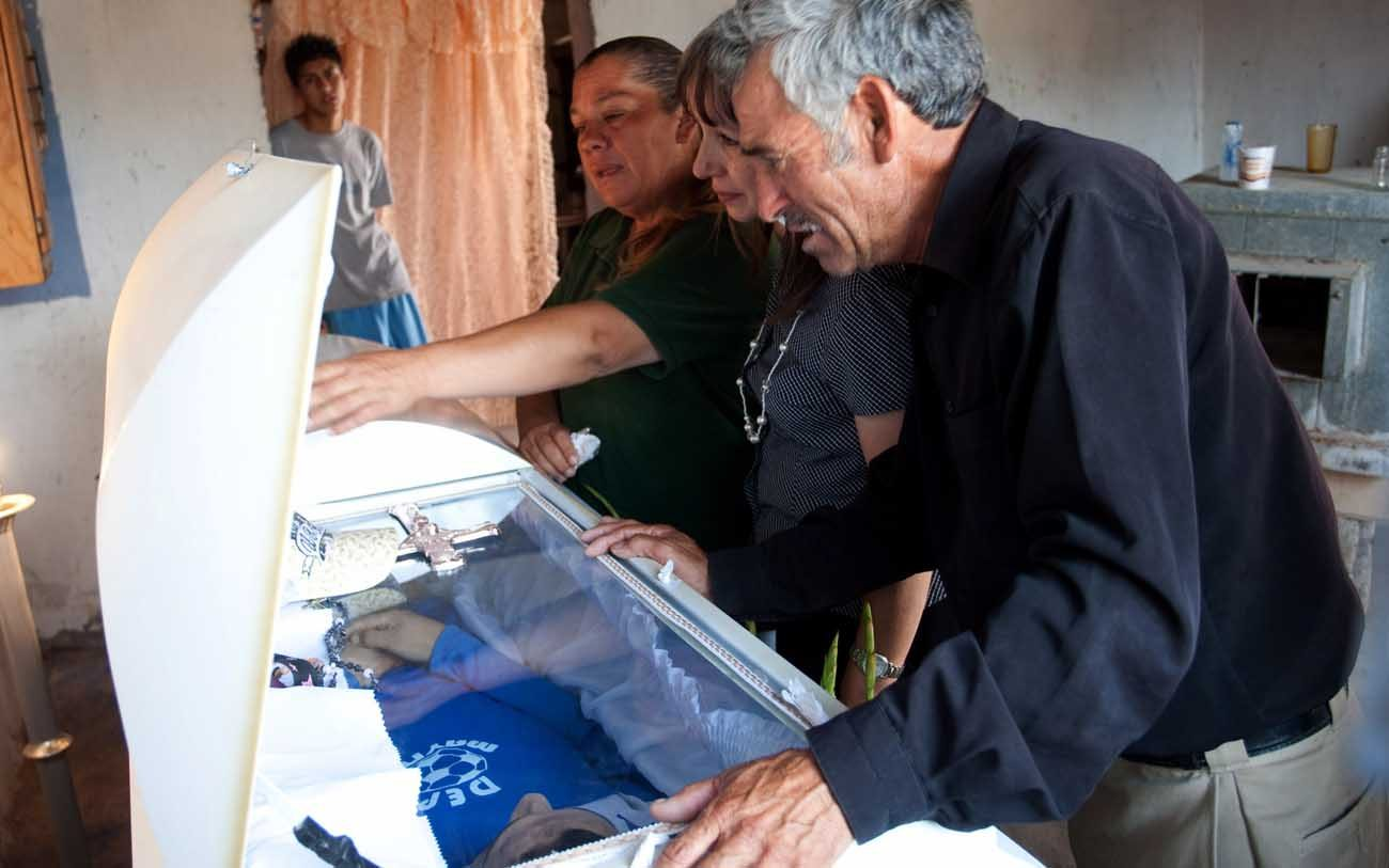 Maria Guadalupe Huereca, left, and Sergio Adrian Hernandez, look at the coffin of their son, 15-year-old Sergio Adrian Hernandez Guereca, during his 2010 wake in Ciudad Juarez, Mexico. The U.S. Supreme Court Feb. 21 heard oral arguments on whether Sergio's parents have the right to sue a U.S. Border Patrol agent who fired across the U.S.-Mexican border and killed their son. (CNS photo/Jesus Alcazar, EPA)