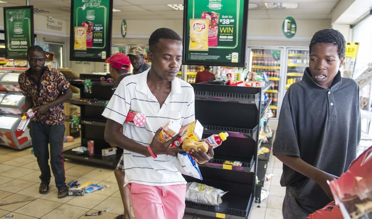 Protesters are seen looting a shop at a gas station in 2016 in Pretoria, South Africa. A South African Catholic commission urged restraint after a spate of xenophobic attacks in South Africa. (CNS photo/Herman Verwey, EPA)