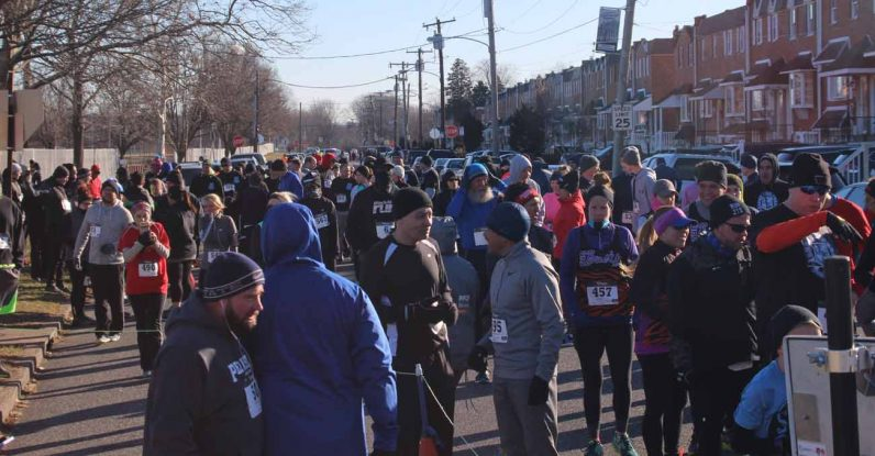 Hundreds of runners gather on Dunks Ferry Road in the city's Parkwood section at the race's starting line.