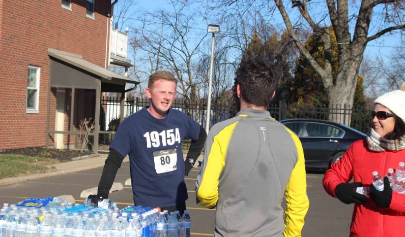 After the race, Father David Friel shares a bottle of well-earned water and conversation with a fellow runner.