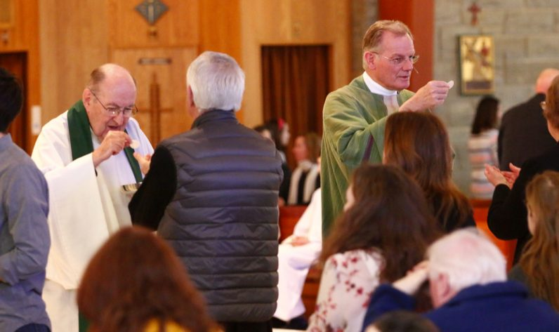 Msgr. Michael Carroll and Msgr. Hans Brouwers distribute holy Communion.