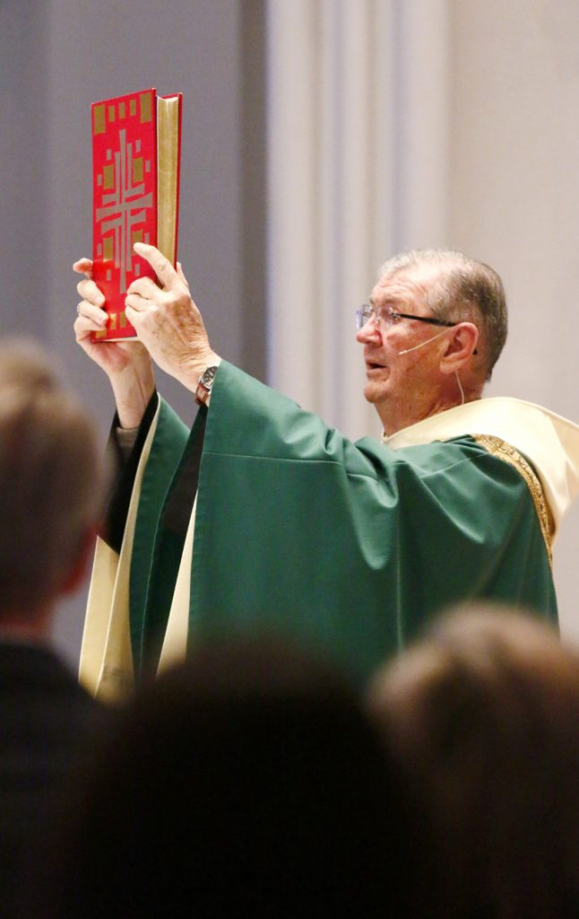 Father Michael Hughes elevates the book of Gospels before proclaiming the reading for the congregation.