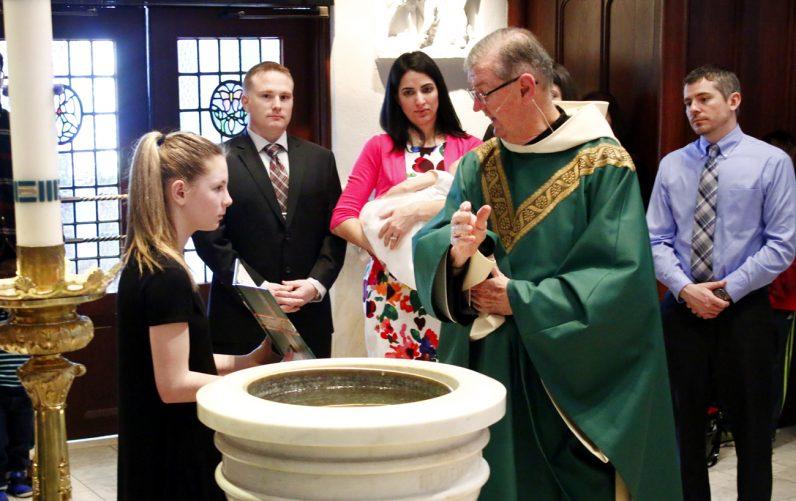 Father Michael Hughes blesses the baptismal water at St. Thomas of Villanova Church.