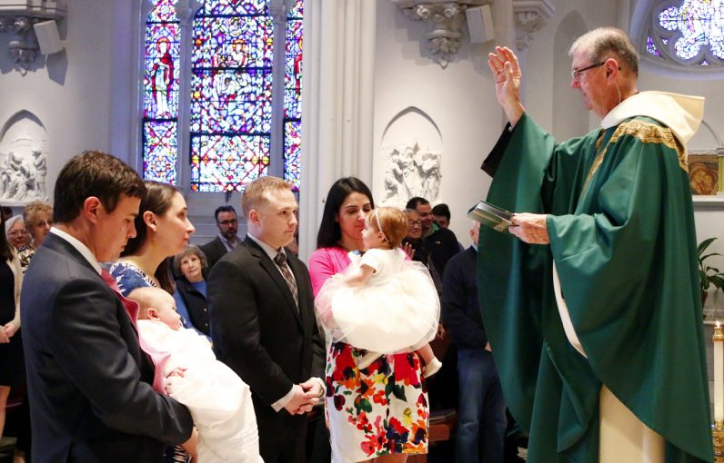 Father Michael Hughes blesses the parents of the newly baptized Madeline Kathleen and Marion Joy.