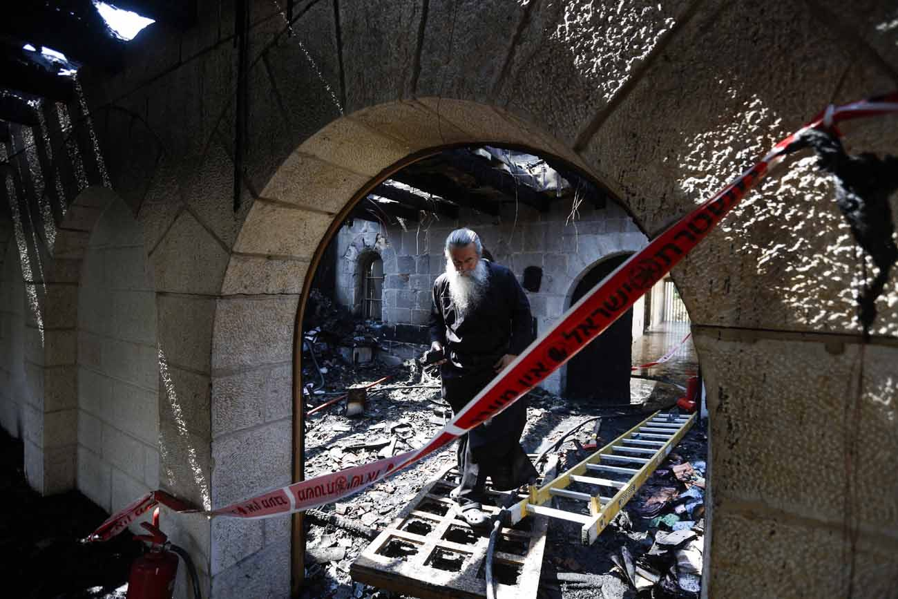A clergyman walks through the rubble of the Church of Loaves and Fishes following a 2015 fire in Tabgha, Israel. Twenty months after the arson attack, the atrium of the Benedictine church was reopened. (CNS photo/Atef Safadi, EPA)