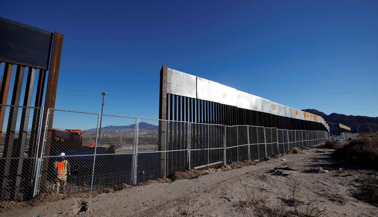 A worker stands next to a newly built section of the U.S.-Mexico border wall in 2016 at Sunland Park, N.M., opposite the Mexican border city of Ciudad Juarez, Mexico.(CNS photo/Jose Luis Gonzalez, Reuters)