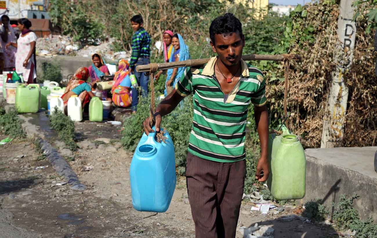 A man carries containers filled with drinking water after taking it from a public tap at a roadside in Jammu, India, May 23, 2016. (CNS photo/Jaipal Singh, EPA)